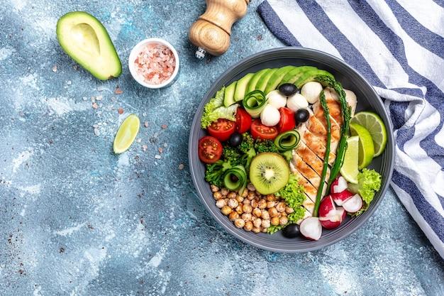 구운 닭고기, 아보카도, 아스파라거스, 병아리 콩, 브로콜리, 무, 오이, 토마토, 올리브, 파란색 배경에 모짜렐라 부처님 그릇, 평면도. 맛있는 균형 잡힌 음식 개념
