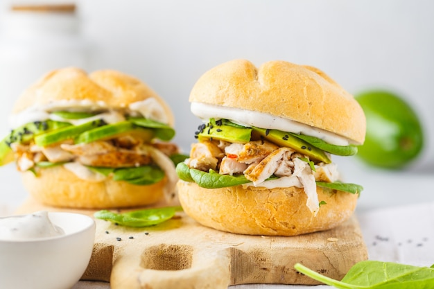 Grilled chicken and avocado burger on wooden board.