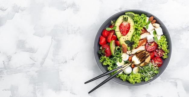 구운 닭고기, 아보카도, 페타 치즈, 메추라기 달걀, 딸기, 견과류, 상추를 흰색 배경에 올려놓고 위쪽 전망을 감상하세요. 맛있는 균형 잡힌 음식 개념. 긴 배너 형식입니다. 평면도.