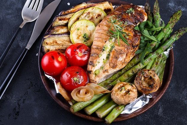Grilled chicken breast on a cast iron skillet with grill vegetables and green sauce on a stone, flat lay