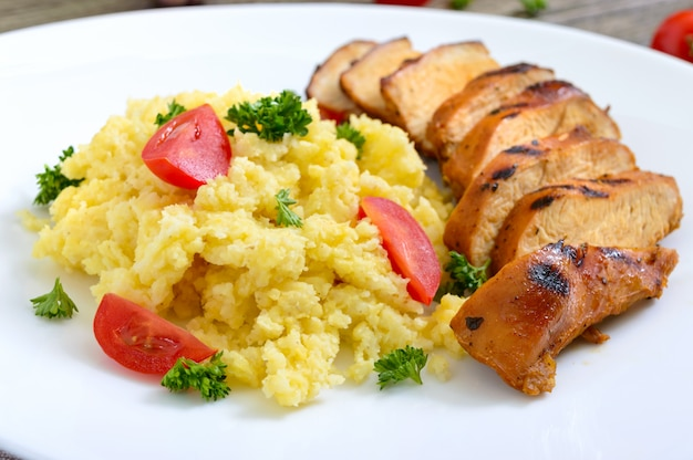 Grilled chicken breast and delicious millet porridge on a white plate. close up