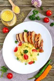 Grilled chicken breast and delicious millet porridge on a white plate on a wooden table. top view