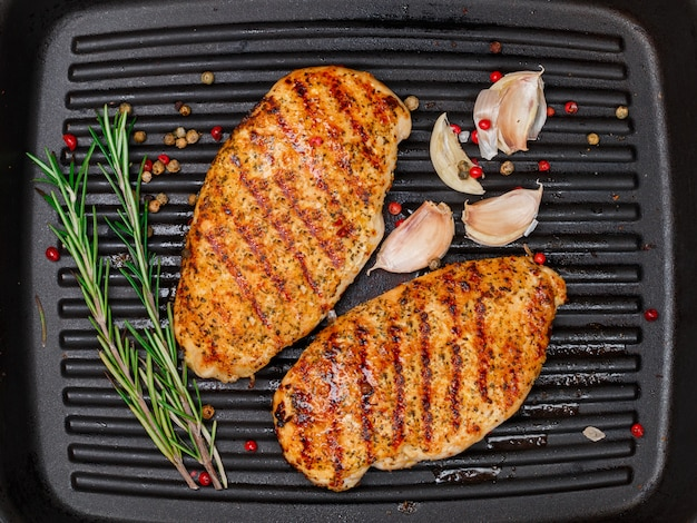 Grilled chicken breast (fillet) with garlic, herbs rosemary, pepper peas on the grill pan