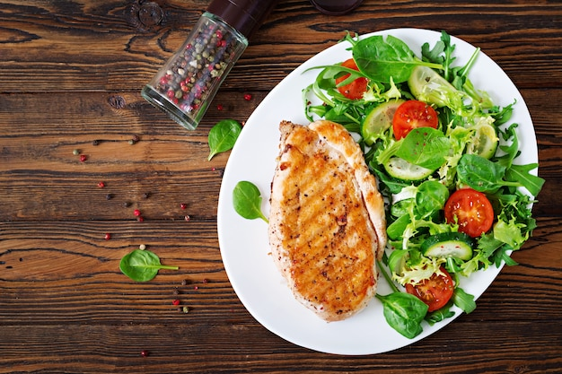 Grilled chicken breast and fresh vegetable salad - tomatoes, cucumbers and lettuce leaves. chicken salad. healthy food. flat lay. top view
