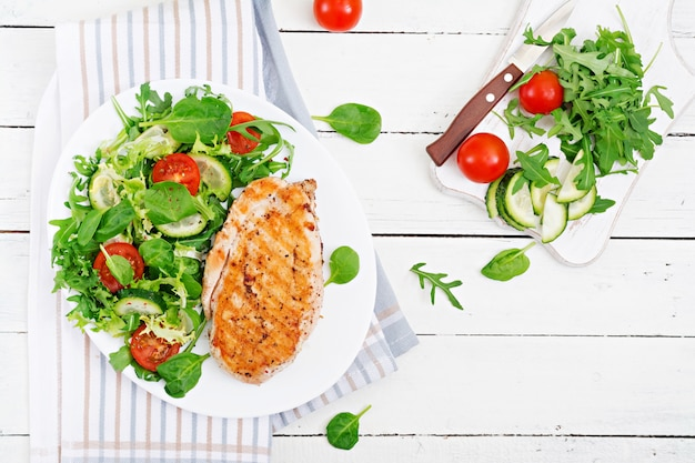 Grilled chicken breast and fresh vegetable salad - tomatoes, cucumbers and lettuce leaves. chicken salad. healthy food. flat lay.