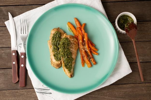 Жареная куриная грудка, зелень и морковь на зеленой тарелке.
