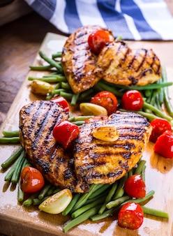Куриная грудка гриль в разных вариациях с помидорами черри, зеленой фасолью, чесночными травами, нарезанным лимоном на деревянной доске или тефлоновой сковороде.