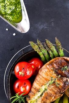 Куриная грудка гриль на чугунной сковороде с овощами гриль и зеленым соусом на каменной поверхности