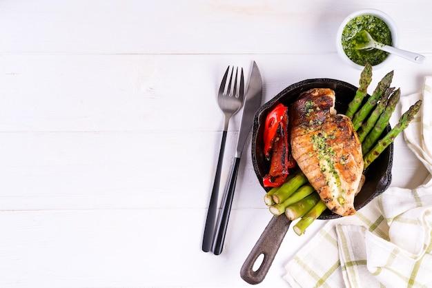 Куриная грудка гриль на чугунной сковороде с овощами гриль на деревянной поверхности