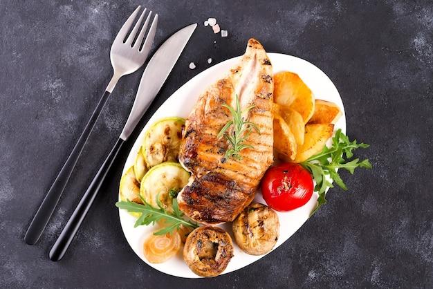Куриная грудка гриль на тарелке с помидорами, грибами на каменной поверхности