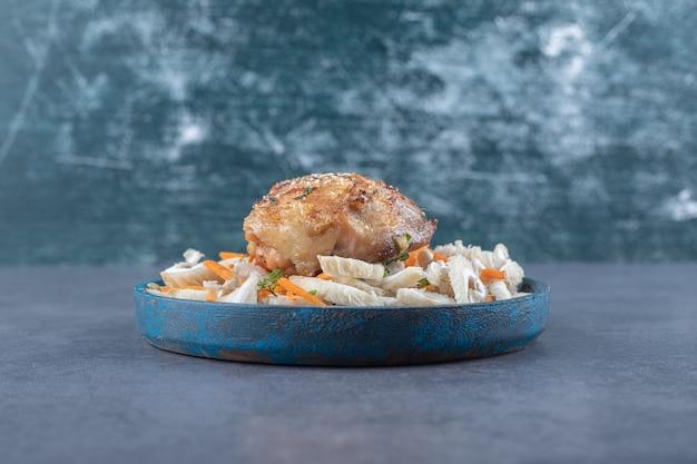 Жареная куриная грудка на синей тарелке.