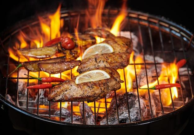 Куриная грудка гриль на пламенном гриле с овощами гриль, помидорами, зеленью, лимоном, розмарином. меню здорового обеда.