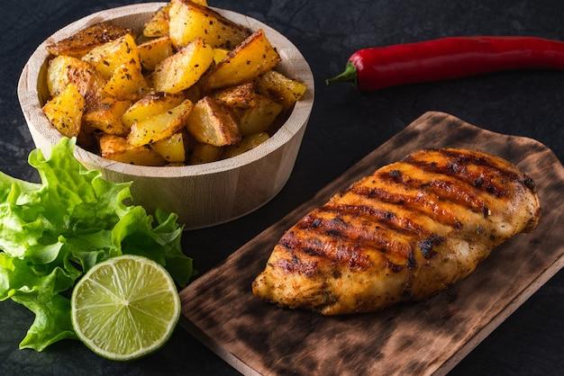 Жареная куриная грудка на деревянной доске и жареный картофель с овощами на черной поверхности