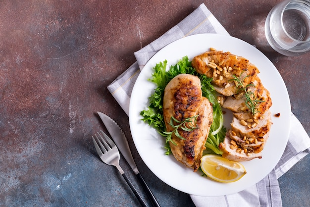 Grilled chicken breast pieces and whole and lemon slice with salad. paleo diet.