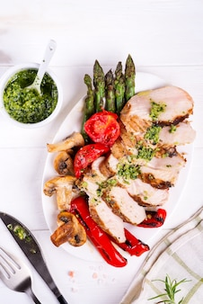 Grilled chicken breast on a plate with tomatoes, asparagus and mushrooms on a plate, flat lay
