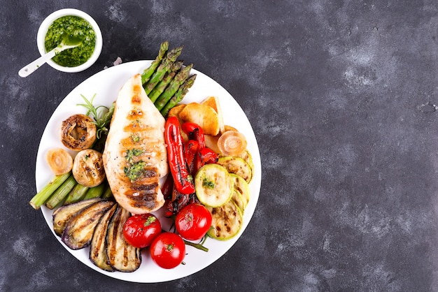 Grilled chicken breast on a plate with tomatoes, asparagus and mushrooms on a stone, flat lay