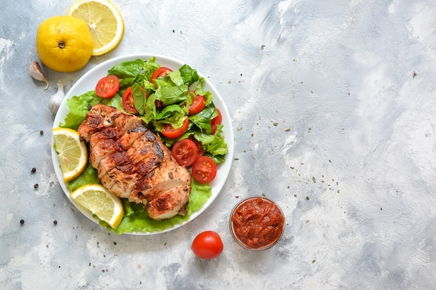 Салат из куриной грудки на гриле со шпинатом и помидорами.