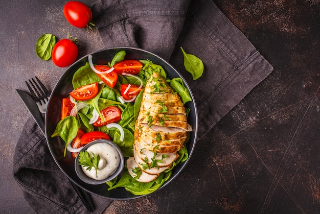 Grilled chicken breast salad with spinach, tomatoes and caesar dressing, dark background.