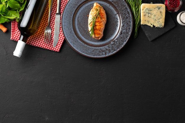 Жареная куриная грудка в тарелке на черном столе