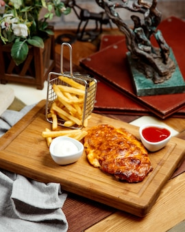 Grilled chicken breast served with french fries mayonnaise and ketchup