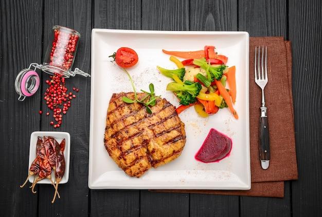 Стейк из куриной грудки на гриле с овощами в ресторане
