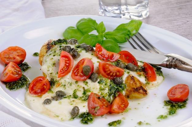Куриная грудка на гриле, покрытая топленым сыром моцарелла, базиликом, песто, помидорами и каперсами