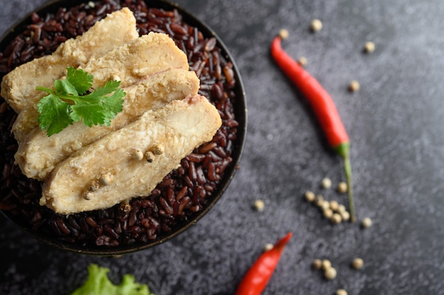 Grilled chicken breast topped with pepper on ripe purple rice berries.