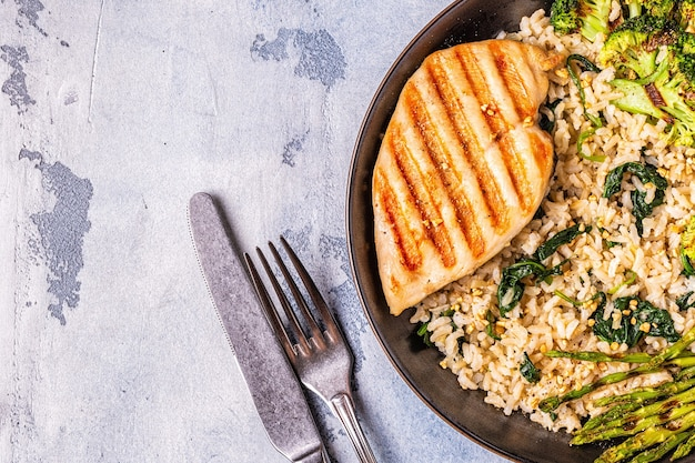 Grilled chicken breast with brown rice spinach broccoli asparagus concept of diet healthy eating