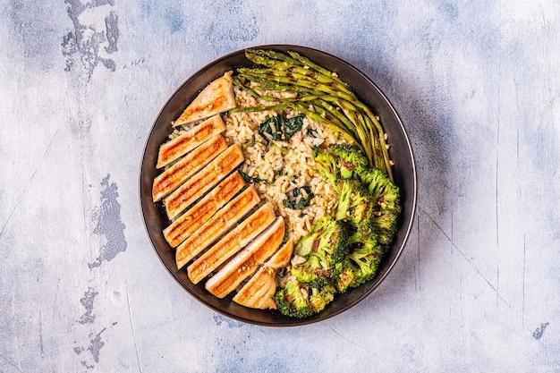 玄米、ほうれん草、ブロッコリー、アスパラガス、食事療法の概念、健康的な食事と鶏胸肉のグリル。