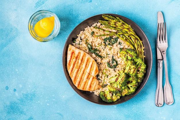 Жареная куриная грудка с коричневым рисом, шпинатом, брокколи, спаржей, концепция диеты, здоровое питание.
