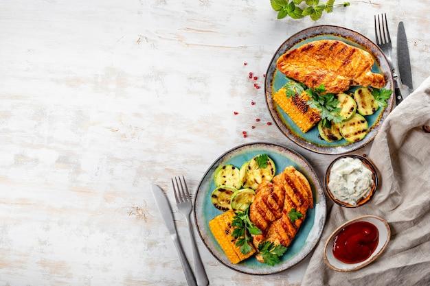 Жареная куриная грудка с кукурузой и цукини на синем фоне сверху. летнее блюдо с курицей гриль и овощами.