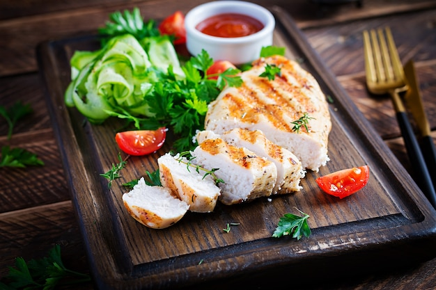 Grilled chicken breast with fresh vegetables on wooden cutting board. healthy dinner. copy space