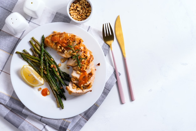 Grilled chicken breast with grilled asparagus and lemon slice on a napkin . paleo diet.