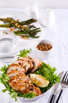Grilled chicken breast with grilled asparagus and lemon slice. paleo diet. healthy nutrition. concept for a tasty and healthy meal.