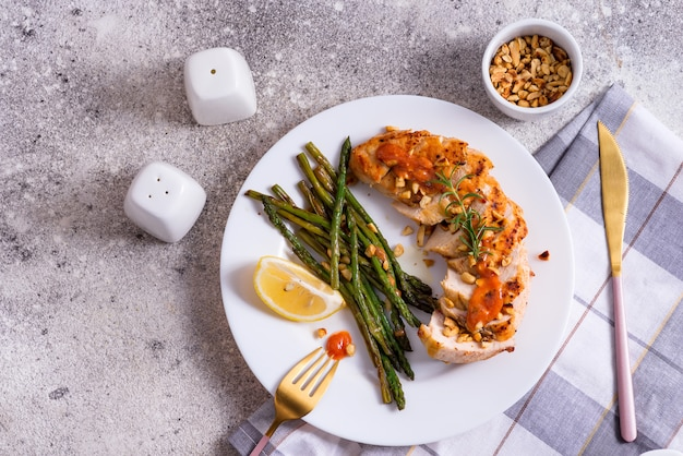 Grilled chicken breast with grilled asparagus and lemon slice. paleo diet.