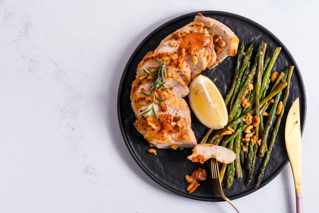 Grilled chicken breast with grilled asparagus and lemon slice . paleo diet.