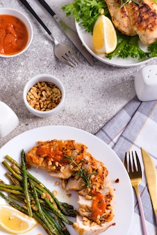 Grilled chicken breast with grilled asparagus and lemon slice, peanuts and sauce. paleo diet.