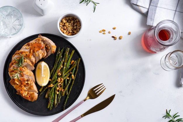 Grilled chicken breast with grilled asparagus and lemon slice on stone. paleo diet. concept for a tasty and healthy meal.