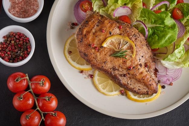 Куриная грудка на гриле с салатными помидорами, зеленью, лимоном, розмарином, луком, нарезанным лимоном на тарелке. меню здорового обеда. диетическое питание.