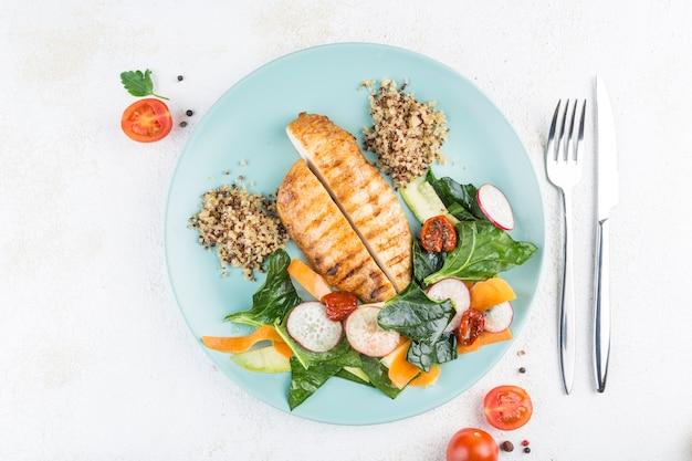 Жареная куриная грудка с киноа, свежим салатом и овощами на зеленой тарелке на светлом фоне. вид сверху с копией пространства для текста. еда из ресторана. горизонтальная ориентация.