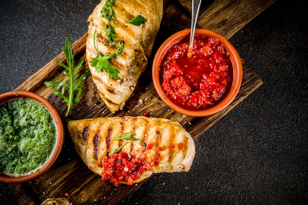Grilled chicken breast with spicy sauces, tomatoes and herbs