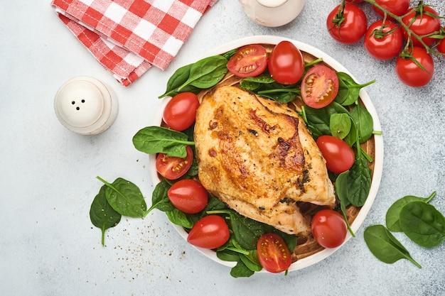 흰색 테이블 배경에 있는 세라믹 접시에 시금치 그린 샐러드, 후추, 체리 토마토를 곁들인 구운 닭 가슴살. 건강 식품, 케톤 생성 식단, 점심 개념. 평면도 및 복사 공간