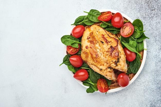 白いテーブルの背景にセラミックプレートでほうれん草のグリーンサラダ、コショウ、チェリートマトと鶏胸肉のグリル。健康食品、ケトン食療法、ランチのコンセプト。上面図とコピースペース