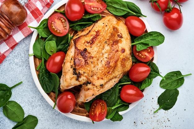 白いテーブルの背景にセラミックプレートでほうれん草のグリーンサラダ、ピーマン、チェリートマトとグリルチキン胸肉。健康食品、ケトン食療法、昼食のコンセプト。上面図とコピースペース。