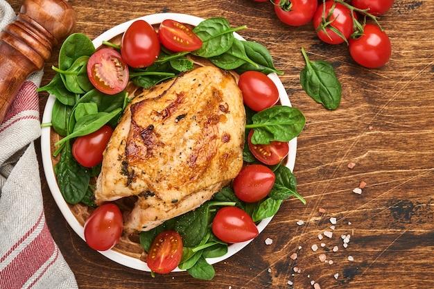 오래된 나무 테이블 배경에 있는 세라믹 접시에 시금치 그린 샐러드, 후추, 체리 토마토를 곁들인 구운 닭 가슴살. 평면도.