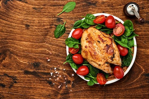 古い木製のテーブルの背景にセラミックプレートでほうれん草のグリーンサラダ、ピーマン、チェリートマトと鶏胸肉のグリル。上面図。