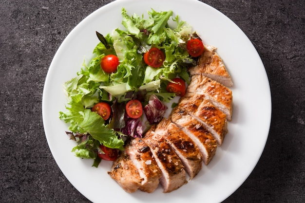 Grilled chicken breast with vegetables on a plate. top view.