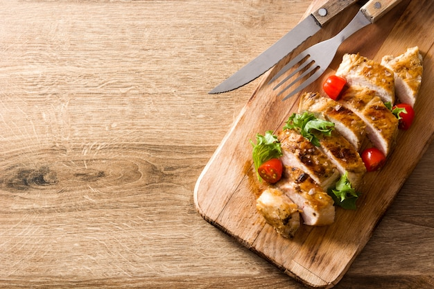 Grilled chicken breast with vegetables on wooden table.