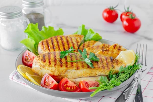Жареные куриные грудки на тарелке с салатом и овощами. диетическое питание.