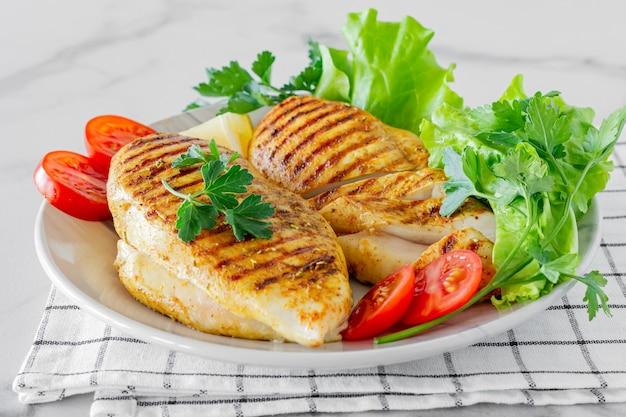 구운 닭 가슴살은 샐러드와 야채와 함께 접시에 제공됩니다.